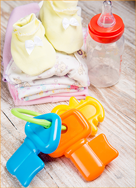 Baby bottle, toys, booties, and blanket